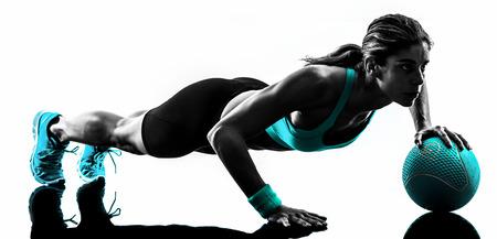 pesas: una mujer caucásica que ejercita la bola de medicina de la aptitud en el estudio de la silueta aislado en el fondo blanco Foto de archivo