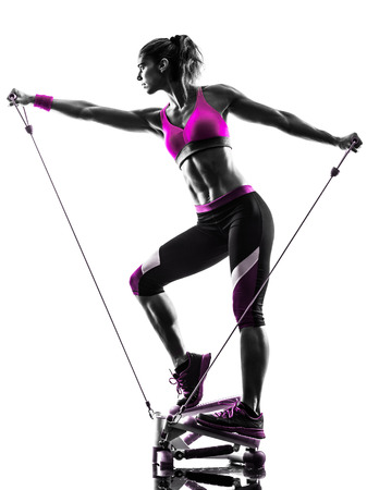 rubber bands: one caucasian woman exercising stepper resistance bands fitness in studio silhouette isolated on white background