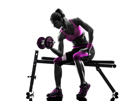 full body woman: one caucasian woman exercising   weights body building fitness in studio silhouette isolated on white background Stock Photo