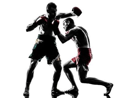 thai boxing: two  men exercising thai boxing in silhouette studio on white background