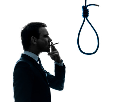 man smoking: one  man smoking cigarette standing in front of hangmans noose in silhouette studio isolated on white background Stock Photo