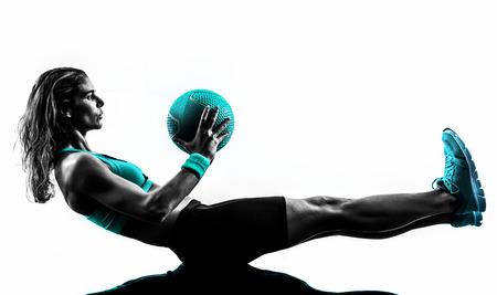 mujeres fitness: una mujer caucásica que ejercita la bola de medicina de la aptitud en el estudio de la silueta aislado en el fondo blanco Foto de archivo