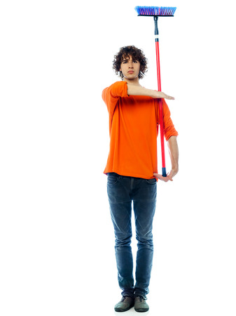 one young man  holding saluting broom portrait in studio white background photo