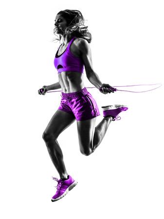 Una mujer caucásica ejercicio de salto de la aptitud de la cuerda en la silueta del estudio aislada en el fondo blanco Foto de archivo - 35651144