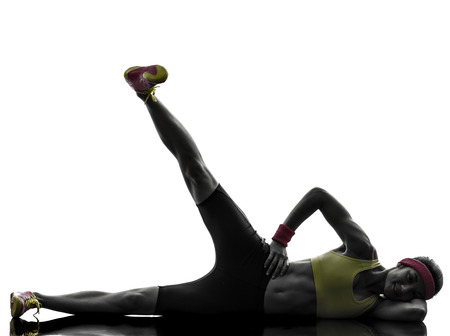 situps: one woman exercising fitness workout legs in the air lying on side in silhouette on white background