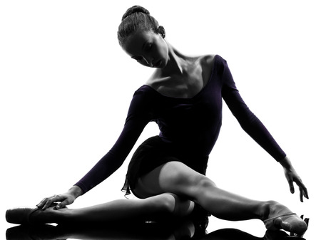 warming up: one  young woman ballerina ballet dancer stretching warming up in silhouette studio on white background Stock Photo