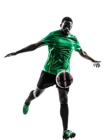 african american silhouette: one african man soccer player green jersey kicking in silhouette on white background