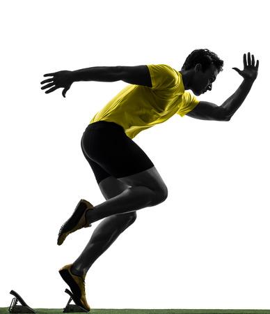 スターティング ブロックで 1 つの男の若いスプリンター ランナーのシルエットの白い背景の上のスタジオ