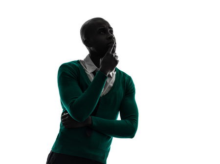 black man thinking: one african black man thinking pensive in silhouette studio on white background Stock Photo