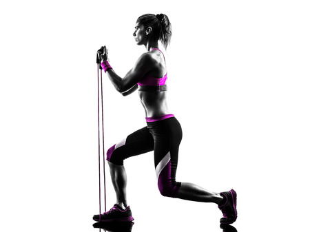 lunges: one caucasian woman exercising  fitness resistance bands in studio silhouette isolated on white background Stock Photo