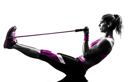 one caucasian woman exercising  fitness resistance bands in studio silhouette isolated on white background Zdjęcie Seryjne