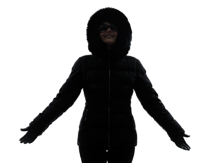 parka: one woman in winter coat arms outstretched happy silhouette on white background Stock Photo