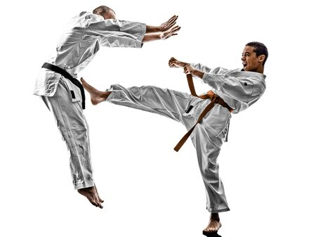 fighting arts: two karate men sensei and teenager student fighters fighting isolated on white background