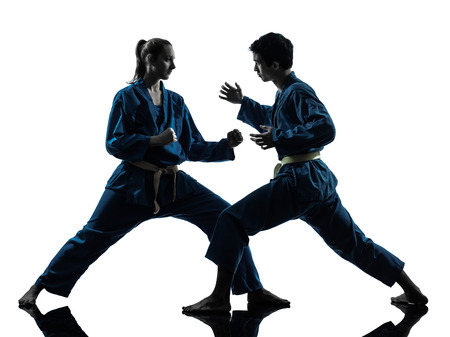 one man woman couple exercising karate vietvodao martial arts in silhouette studio isolated on white background photo