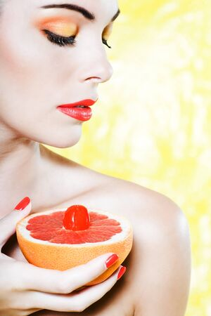 beautiful  woman portrait showing grapefruit breast studio on yellow background photo