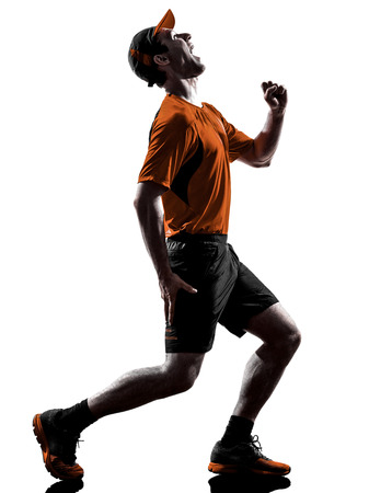 cramps: one young man runner jogger running injury pain cramps in silhouette isolated on white background Stock Photo