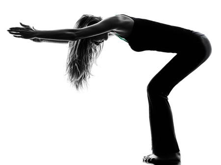 warming up: one woman dancer stretching warming up exercises in studio silhouette isolated on white background Stock Photo