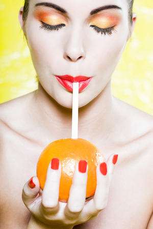 beautiful  woman portrait orange drink with a straw studio on yellow background photo