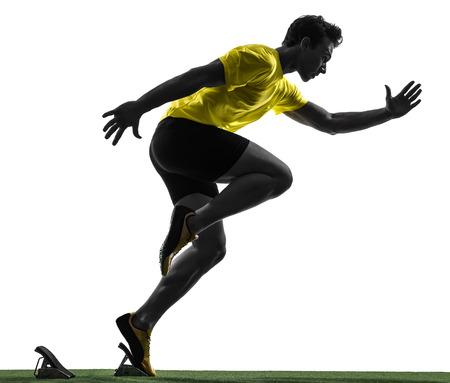 Ein Mann junge Sprinter Läufer in Startlöchern Silhouette Studio auf weißem Hintergrund Standard-Bild