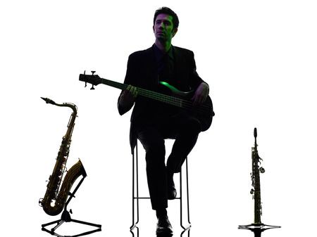bassist: one caucasian man guitarist bassist player playing in studio silhouette isolated on white background Stock Photo