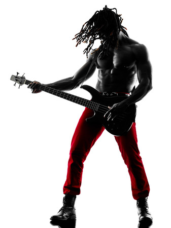 guitarists: one african man guitarist bassist player playing in studio silhouette isolated on white background
