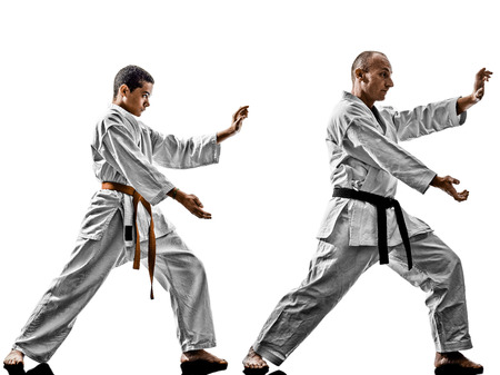 sensei: two karate men sensei and teenager student teacher teaching isolated on white background