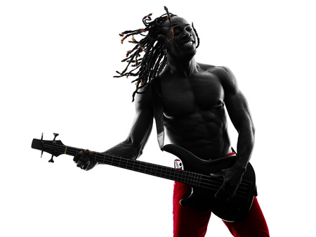 bass player: one african man guitarist bassist player playing in studio silhouette isolated on white background
