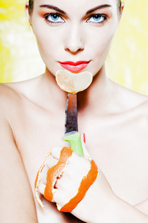 beautiful woman portrait holding a orange tangerine fruit slice with knife studio on yellow background photo