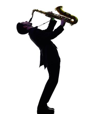 saxof�n: saxofonista saxofonista de juego de un hombre cauc�sico en el estudio de la silueta aislado en el fondo blanco