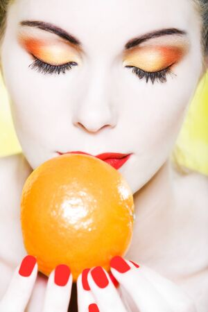 beautiful  woman portrait smelling a mandarin in sutdio photo