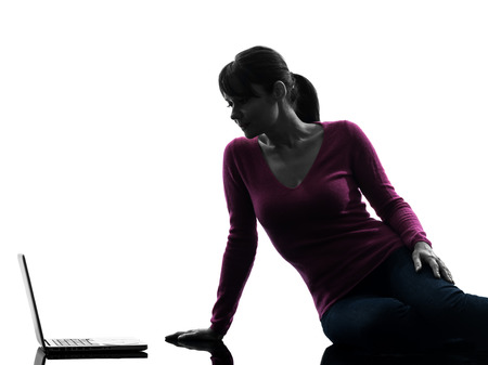 one  woman serious computing laptop computer in silhouette studio isolated on white background photo