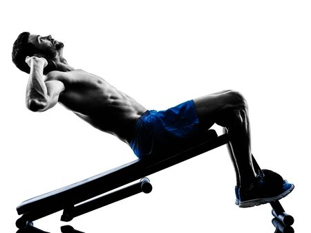 nude abs: one caucasian man exercising fitness crunches crunches Bench Press exercises in studio silhouette isolated on white background