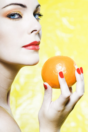 beautiful  woman portrait showing a orange tangerine fruit studio on yellow background photo