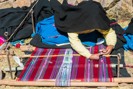 weavers: Puno, Peru - July 25, 2013: woman weaving in the peruvian Andes at Taquile Island on Puno Peru at july 25th, 2013.