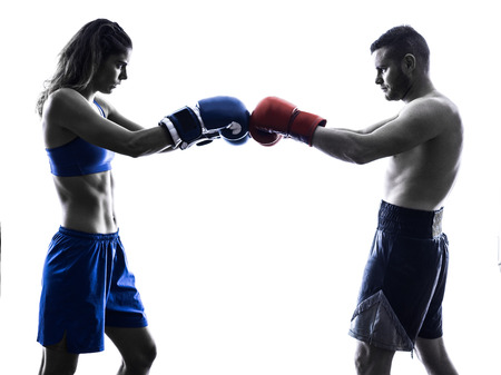 kickboxing: one woman boxer boxing one man  kickboxing in silhouette isolated on white background