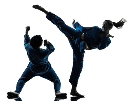 artes marciales: un hombre mujer Pareja ejercicio artes marciales karate vietvodao en estudio de la silueta aislado en el fondo blanco