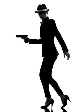 mujer con pistola: una mujer elegante en traje de la celebración de armas en silueta sobre fondo blanco