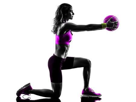 one caucasian woman exercising Medicine Ball  fitness in studio silhouette isolated on white background Stock Photo