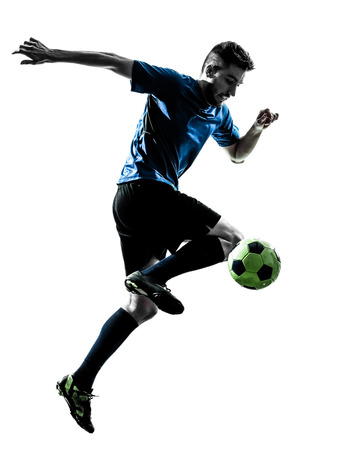 one  soccer player man juggling ball in silhouette isolated white background Фото со стока