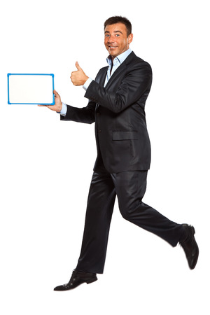 holding blank sign: one  business man running jumping double thumbs up holding whiteboard in studio isolated on white background Stock Photo