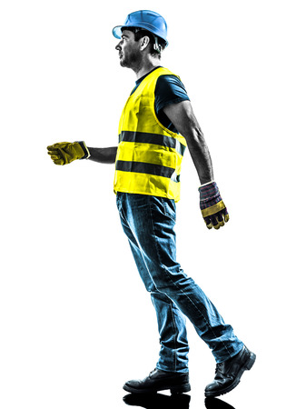 profile view: one construction worker walking with safety vest silhouette isolated in white background