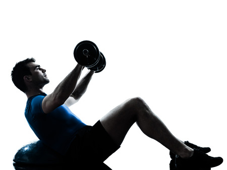 backlit: one  man exercising weight training on bosu workout fitness in silhouette studio isolated on white background