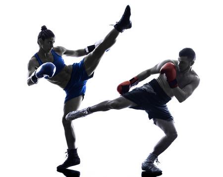 一人の女性ボクサーがボクシングの白い背景で隔離のシルエットで 1 つの男のキック ボクシング