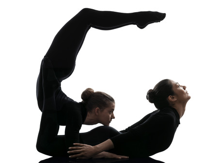 suppleness: two women contortionist practicing gymnastic yoga in silhouette on white background Stock Photo
