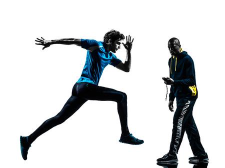 corriendo: un hombre corriendo carreras de velocidad con el entrenador cron�metro en estudio de la silueta aislado en el fondo blanco