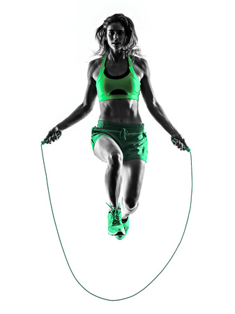 one caucasian woman exercising  Jumping Rope fitness in studio silhouette isolated on white background Stock Photo