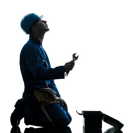 obrero trabajando: un reparador trabajador desesperación orando silueta en estudio en el fondo blanco