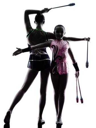 rhythmische sportgymnastik: eine Frau kaukasisch Teenager und M�dchen Kind Aus�bung der Rhythmischen Sportgymnastik in Silhouette isoliert auf wei�em Hintergrund Lizenzfreie Bilder