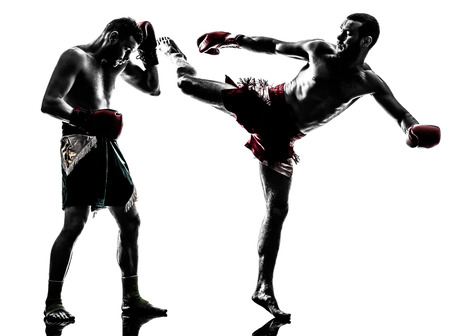 fighting arts: two  men exercising thai boxing in silhouette studio on white background