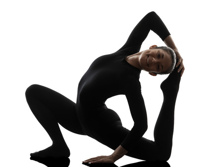 contortionist: one  woman contortionist practicing gymnastic yoga in silhouette on white background